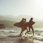 カウアイで友人とのサーフィンをする女性