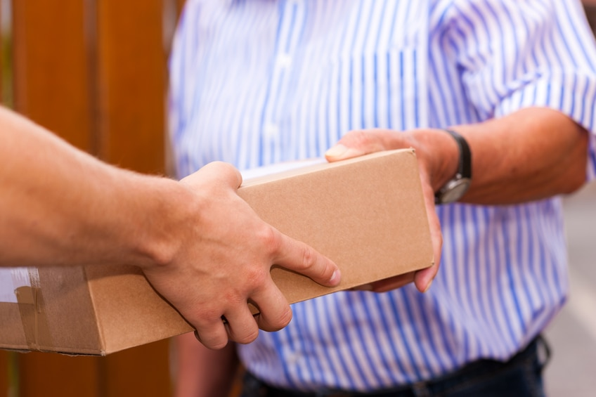 Postal service - delivery of a package; the postman is giving the package to the customer (only hands and package to be seen)