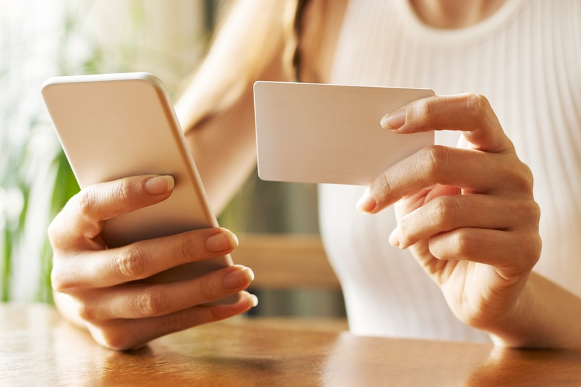 Woman with mobile phone shopping online.