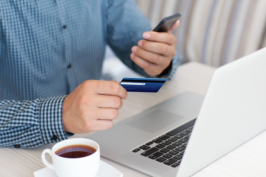man makes the payment by credit card on the laptop and holding phone