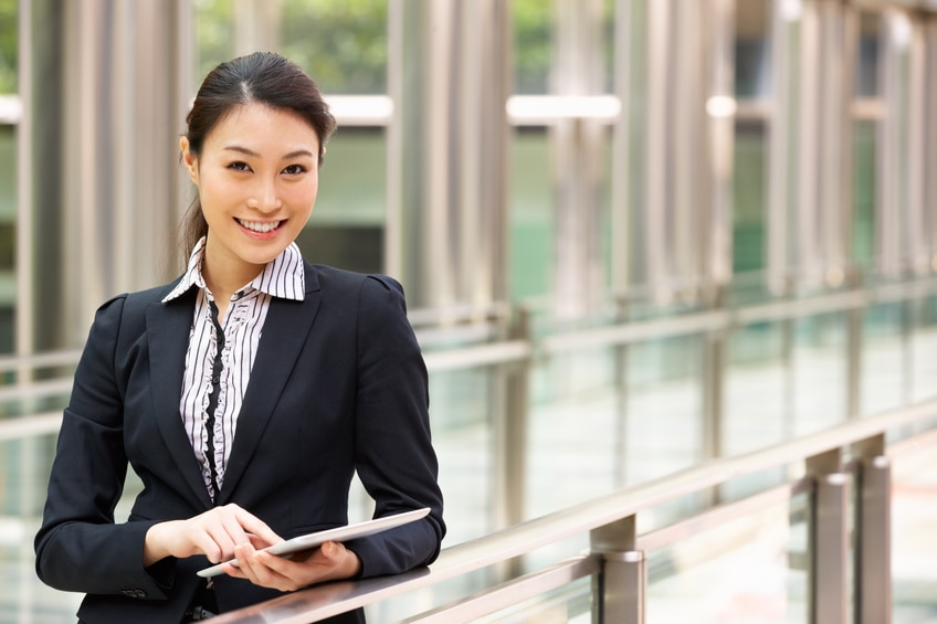 Chinese Businesswoman Working On Tablet Computer Outside Office Looking At Camera Smiling