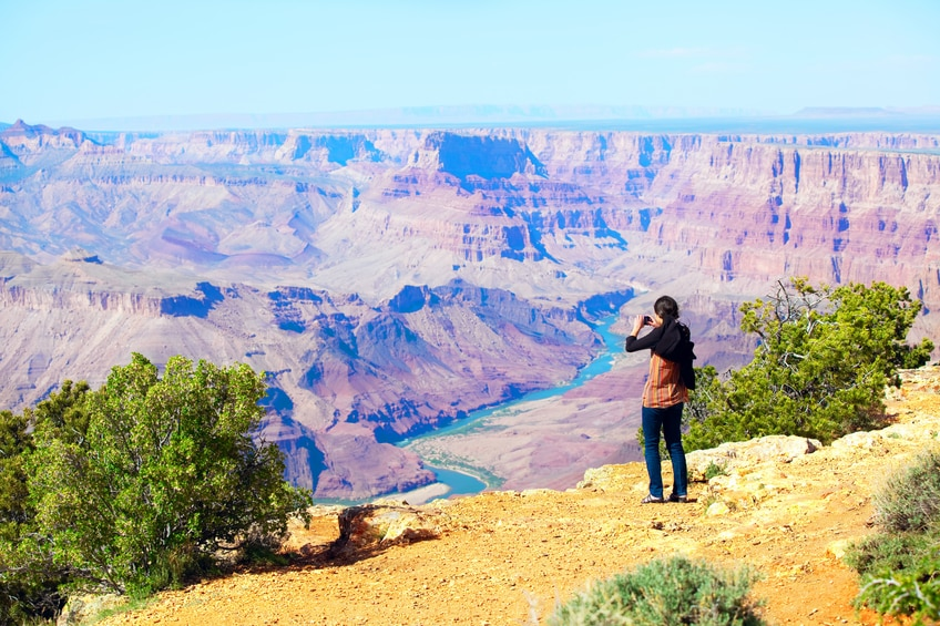 Teen girl taking pictures at the Grand Canyon with cell phone.