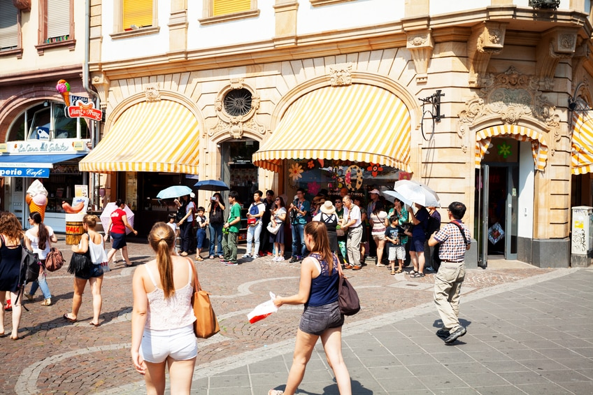 Frankfurt, Germany - July 3, 2015: Summertime shot of walking people and a large group of asian tourists near shop in inner city of Frabnkfurt. Scene is near Berliner Str and Neue Kräme.